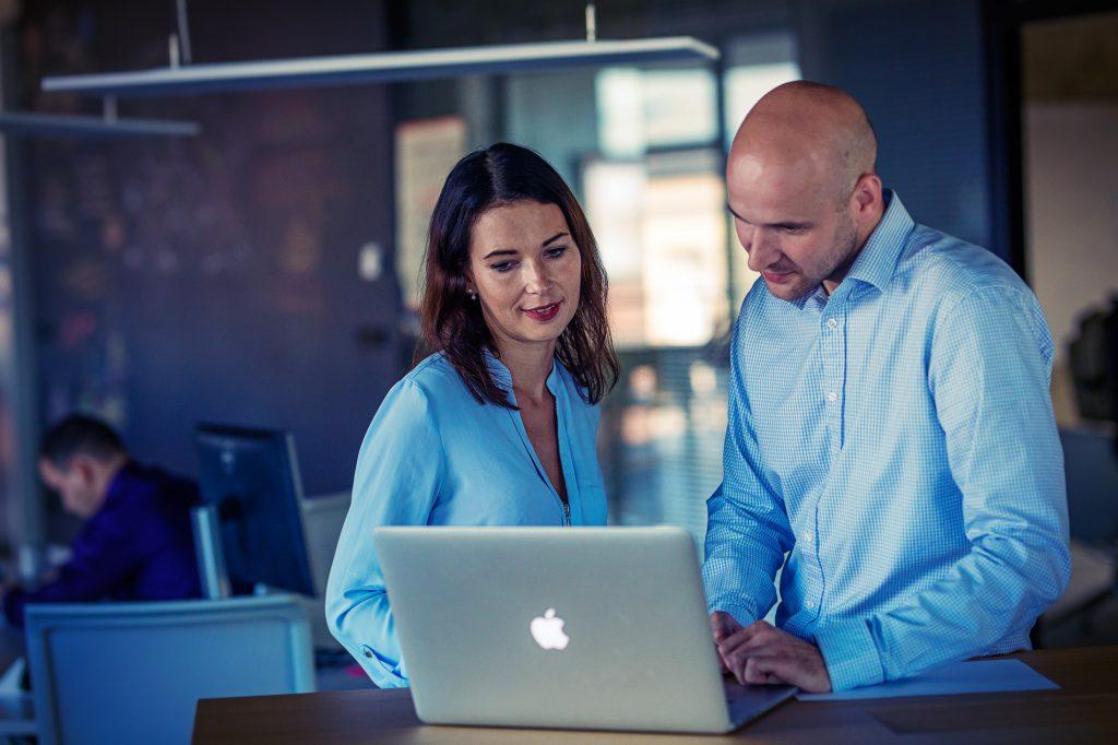 Woman and man smiling at laptop