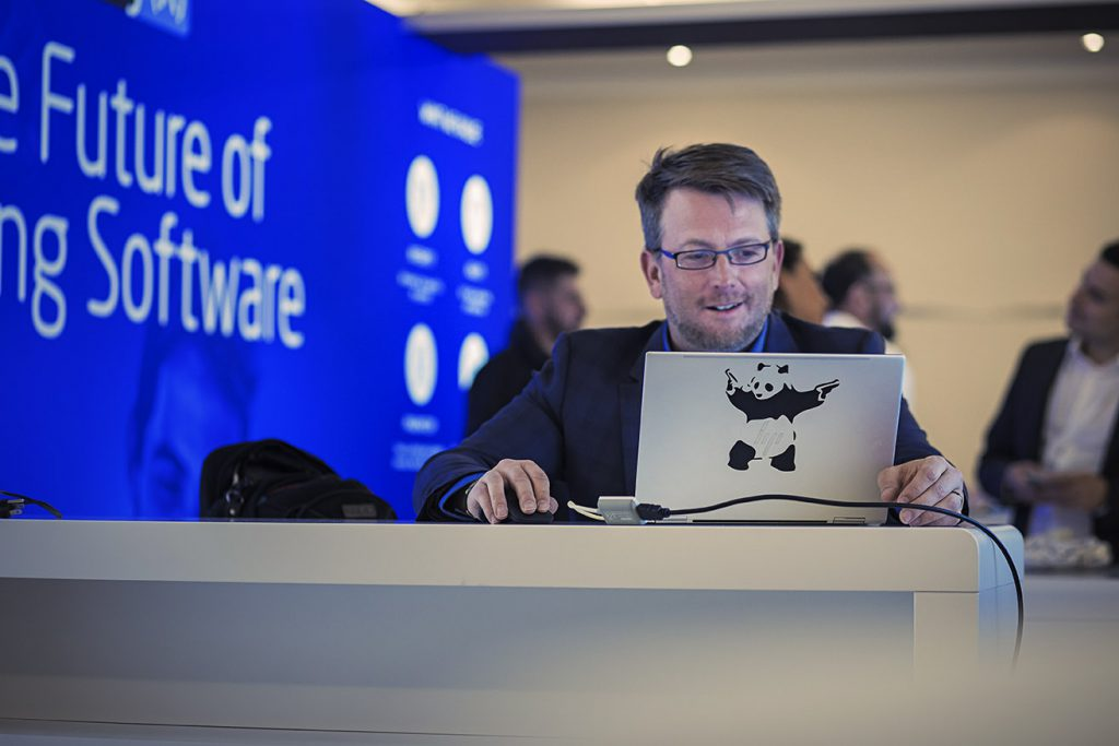 Man on laptop at software conference