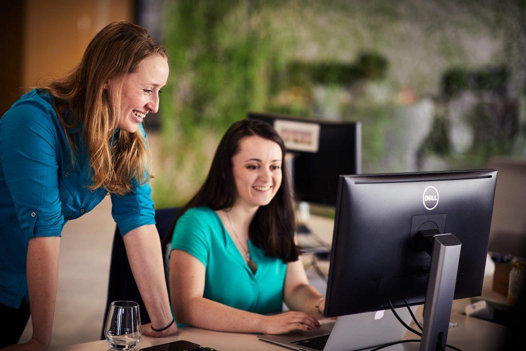 Two women laughing at laptop